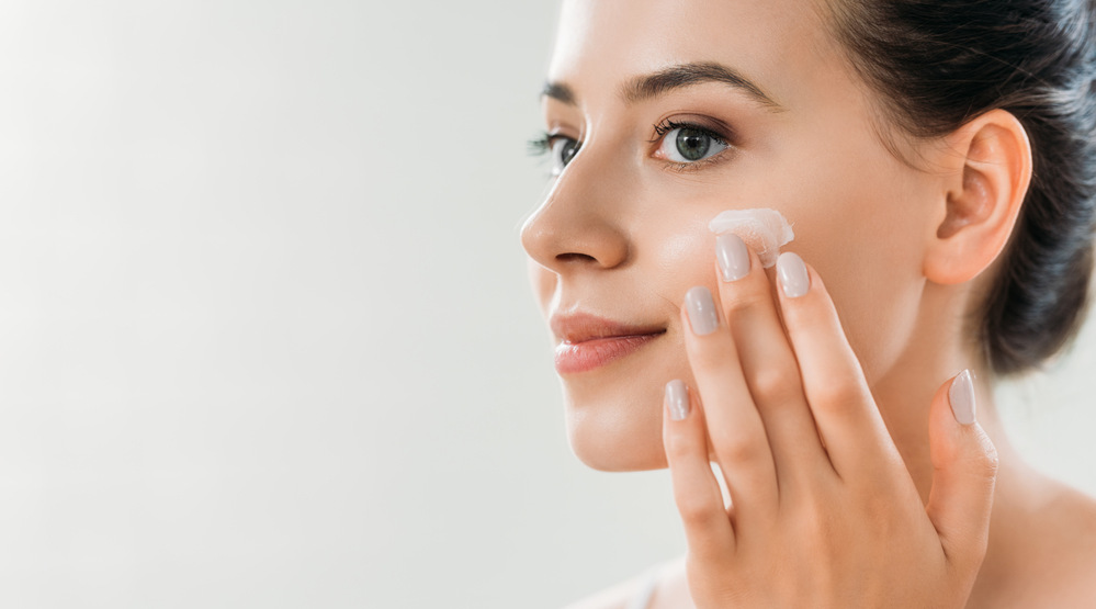 woman cares for skin with cream